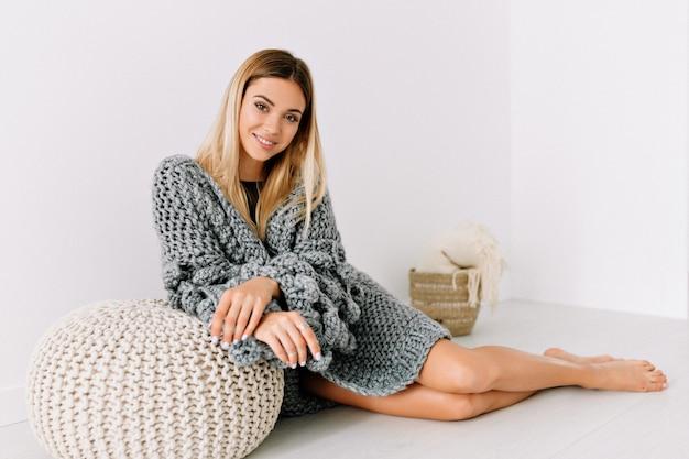 Geweldige mooie vrouw in trendy trui op de vloer liggen en glimlachen