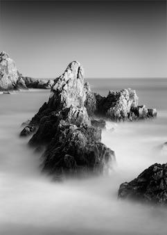 Geweldige opname in grijstinten van een rotsachtig strand in guernsey