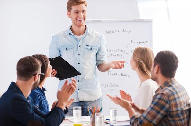 Geweldige presentatie! groep zakenmensen in slimme vrijetijdskleding die samen aan tafel zitten en applaudisseren voor hun collega die bij het whiteboard staat en glimlacht