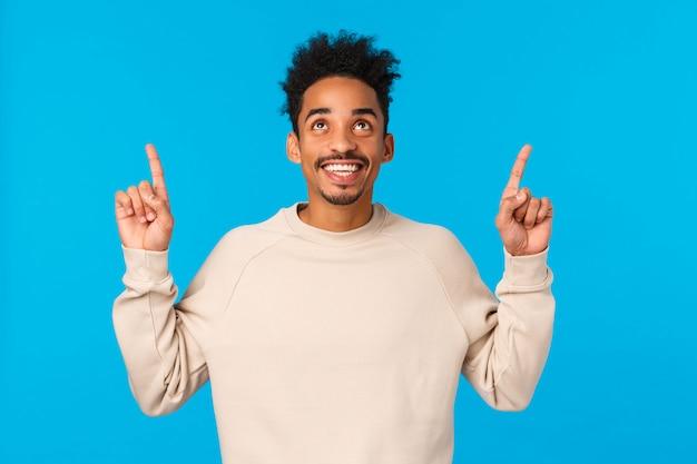 Geweldige promo. verbaasd, opgewonden lachende gelukkige afro-amerikaanse man met afro hipster kapsel, snor, op zoek naar boven bewonderend uitzicht, vond uitstekend cadeau voor valentijnsdag, blauw