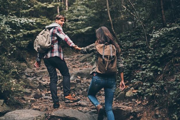 Geweldige reis! achteraanzicht van een modern jong stel dat handen vasthoudt en omhoog beweegt terwijl ze samen wandelen in het bos