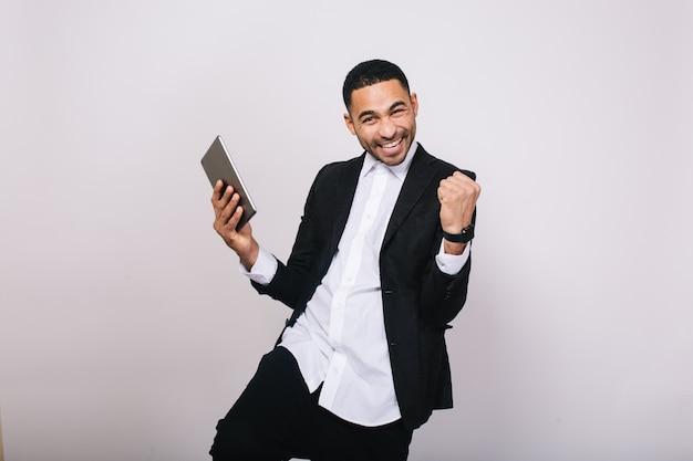 Geweldige resultaten behalen op het werk, succes in de carrière van een knappe jongeman in een wit overhemd, een zwart jasje dat geluk uitdrukt. stijlvolle zakenman, modern, vrolijk, glimlachend.