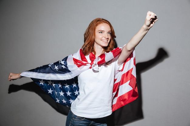 Geweldige roodharige jonge dame superheld met amerikaanse vlag