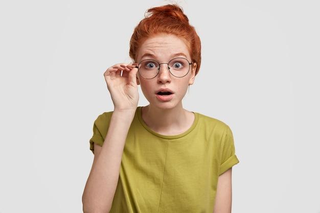 Geweldige roodharige vrouw met een verbijsterde uitdrukking, staart door een bril, opent de mond een beetje, ziet iets verrassends