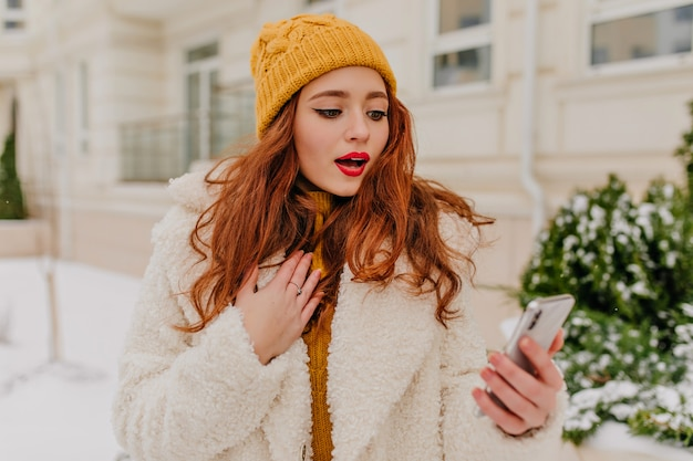 Geweldige roodharige vrouw met telefoon op straat. leuke gemberdame in jas en hoed met smartphone.