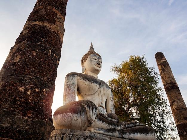 Geweldige scène van een groot boeddhabeeld en een oude oude structuur in de wat mahathat-tempel in het district sukhothai historical park, een unesco-werelderfgoed in thailand.