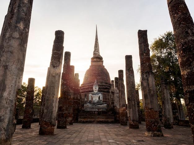Geweldige scène van een groot boeddhabeeld en oude oude ruïnes in de wat mahathat-tempel in het district sukhothai historical park, een unesco-werelderfgoed in thailand.