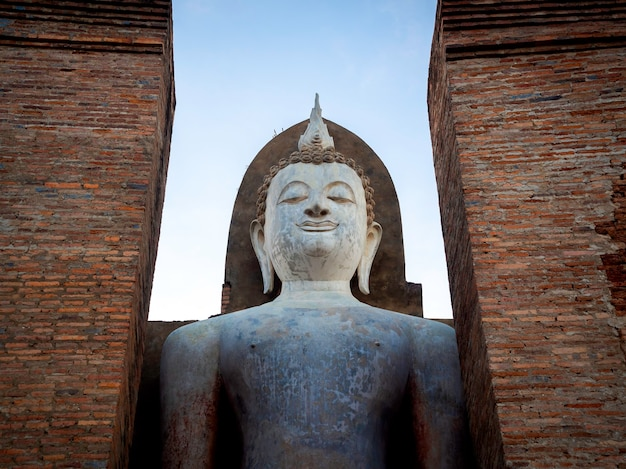 Geweldige scène van een groot staand boeddhabeeld en een oude oude constructie in de wat mahathat-tempel in het district sukhothai historical park, een unesco-werelderfgoed in thailand.