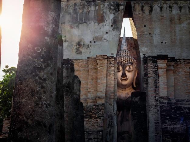 Geweldige scène van het oude grote boeddhabeeld in de oude kerk met ruïnes in de wat sri chum-tempel, de beroemde bezienswaardigheid in het sukhothai historical park, een unesco-werelderfgoed in thailand.