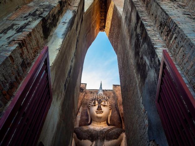 Geweldige scène van het oude grote boeddhabeeld in de oude kerk van de wat sri chum-tempel, de beroemde bezienswaardigheid in het sukhothai historical park, een unesco-werelderfgoed in thailand.