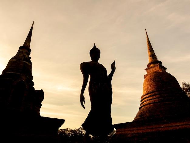 Geweldige scène van silhouet van boeddhabeeld en oude oude pagode bij wat sra sri en tra pang tra kuan-tempel in het district van sukhothai historical park, een unesco-werelderfgoed in thailand.