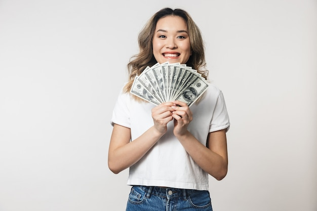 Geweldige schattige jonge vrouw poseren geïsoleerd over witte muur muur met geld