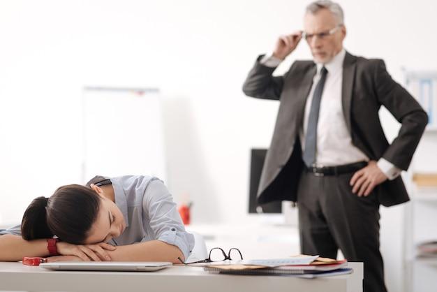 Geweldige secretaresse die de ogen gesloten houdt tijdens het slapen op de werkplek, leunend op de tafel