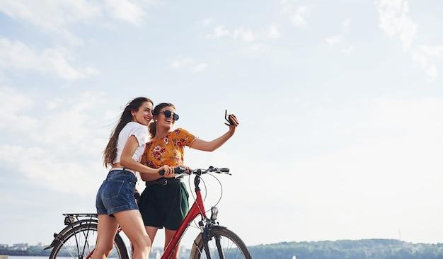 Geweldige selfie maken. twee vriendinnen op de fiets hebben plezier op het strand bij het meer.