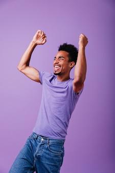 Geweldige sterke kerel die schreeuwt. binnen schot van gelukkig afrikaanse man in casual t-shirt.