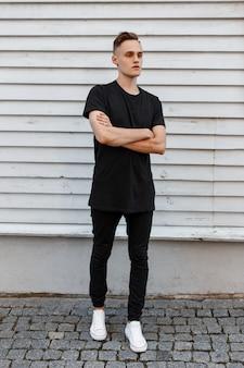 Geweldige stijlvolle jongeman in een zwart stijlvol t-shirt in trendy spijkerbroek in witte sneakers vormt in de buurt van een wit houten vintage huis