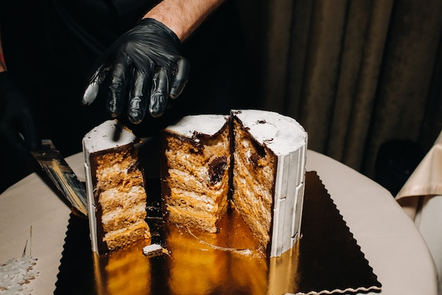 Geweldige taarten. een chef-kok met zwarte handschoenen snijdt een chocoladebruidstaart. de bruidstaart is heerlijk van binnen op een zwarte ondergrond. grote taart in witte chocolade.