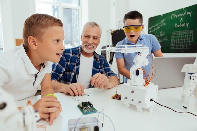Geweldige technologie. slimme, aardige jongen die naar de robot kijkt terwijl hij er enthousiast over is