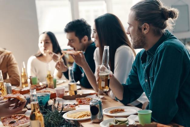Geweldige tijd met vrienden. groep jongeren in vrijetijdskleding die pizza eet en glimlacht terwijl ze binnen een etentje hebben