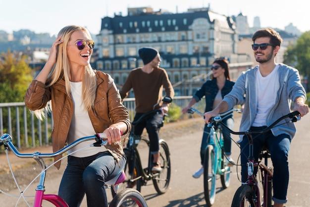 Geweldige tijd met vrienden. mooie jonge glimlachende vrouw die fietst en wegkijkt terwijl haar vrienden op de achtergrond rijden