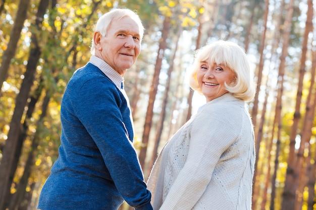 Geweldige tijd samen doorbrengen. achteraanzicht van een gelukkig senior koppel dat handen vasthoudt en over de schouder kijkt terwijl ze samen door het park wandelen