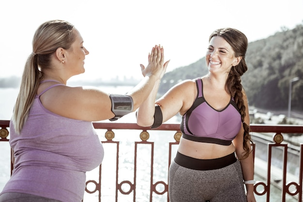 Geweldige training. opgewekte aardige vrouwen die elkaar high five gaven terwijl ze op de brug stonden