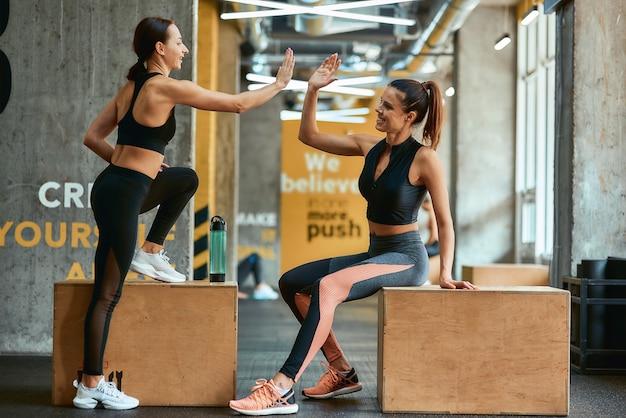 Geweldige training. twee jonge atletische fitnessmeisjes in sportkleding die elkaar high five geven terwijl ze op crossfit-jumpboxen in de sportschool zitten en samen trainen. sport, training en gezonde levensstijl