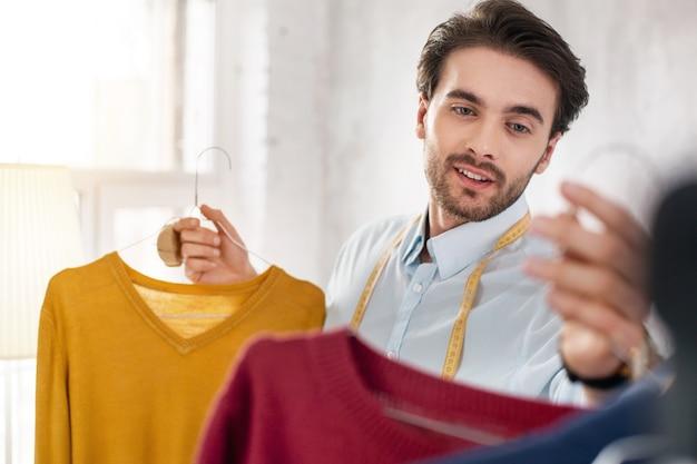 Geweldige uitstraling. vrolijke bebaarde stylist glimlachend en kijken naar de truien in zijn collectie