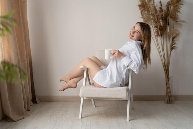 Geweldige vakantie in huis. de jonge mooie vrouw draagt het overhemd van een man. de blonde zit op een fauteuil. drink 's morgens vroeg thee. glimlach op je gezicht