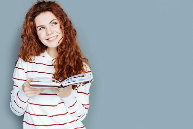 Geweldige verbeeldingskracht. vrolijke mooie dromerige vrouw die een boek vasthoudt en glimlacht terwijl ze geniet van het verhaal