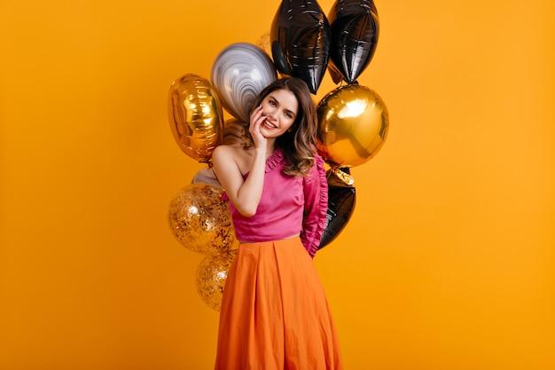 Geweldige verjaardagsvrouw die zich voordeed op oranje muur