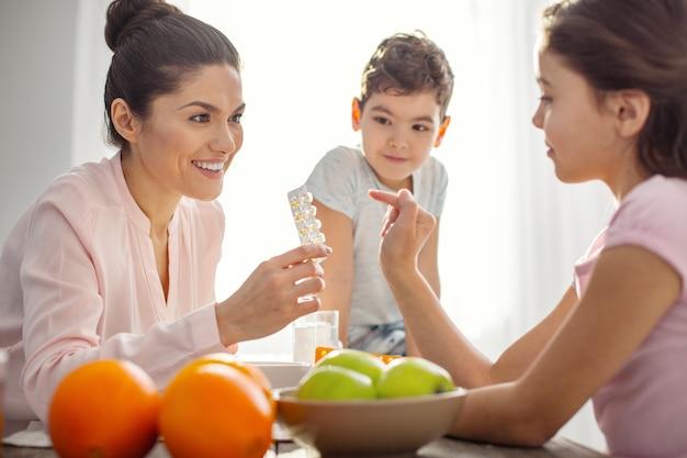 Geweldige vitamines. leuke uitbundige donkerharige jonge moeder die vitamines vasthoudt en met haar kinderen praat over gezondheidszorg en de jongen die op tafel zit