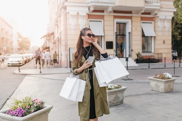 Geweldige vrouw in lange elegante vacht permanent op straat met tassen van boetiek en wegkijken