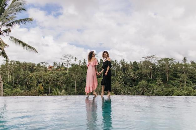 Geweldige vrouw in lange roze jurk staande naast meer. charmante dames hand in hand in de buurt van buitenzwembad met bos