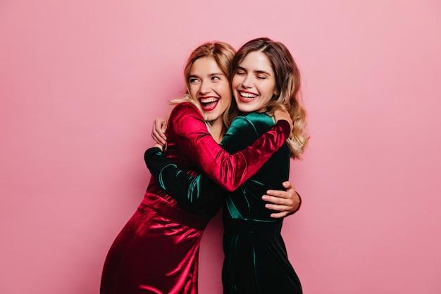 Geweldige vrouw in rood fluwelen jurk omarmen haar zus. verfijnde meisjes die plezier hebben op een roze muur.