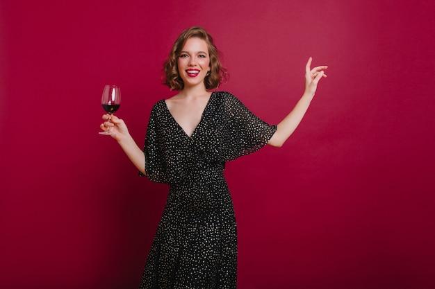Geweldige vrouw in vintage jurk dansen en handen zwaaien op lichte achtergrond