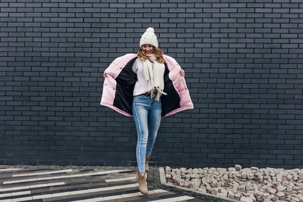 Geweldige vrouw in winter kleding grappig dansen op stedelijke straat. vrouwelijk model in spijkerbroek genieten van fotoshoot in koude dag.