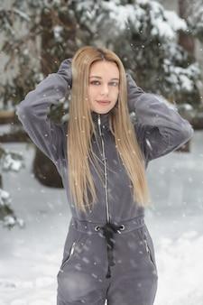 Geweldige vrouw met lang haar poseren in het bos bij sneeuwweer