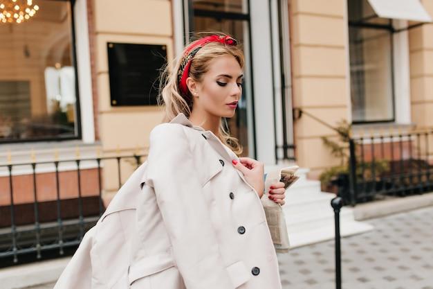 Geweldige vrouw met trendy make-up en manicure lopen op straat en naar beneden te kijken