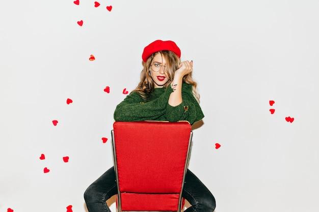 Geweldige vrouw met zelfverzekerde gezichtsuitdrukking zittend op rode stoel