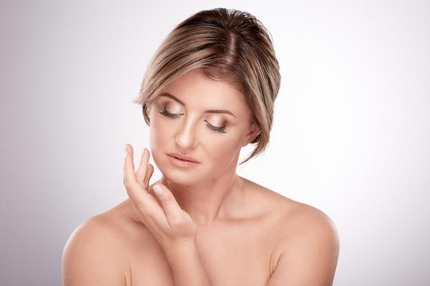 Geweldige vrouw van gemiddelde leeftijd met naakt make-up en naakte schouders poseren muur, schoonheidsfoto concept, huid en rimpels behandeling, gezicht aanraken.