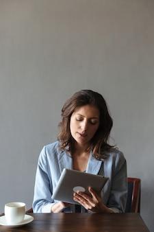 Geweldige vrouw zitten binnenshuis met behulp van tablet-computer.