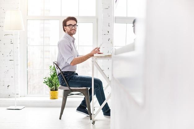 Geweldige werkdag. vrolijke bebaarde man zit aan de tafel en werkt op zijn laptop
