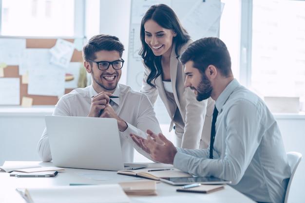Geweldige zakelijke bijeenkomst. drie collega's die iets met een glimlach bespreken terwijl ze op kantoor zitten