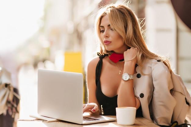 Geweldige zakenvrouw in zwarte jurk en stijlvol polshorloge met laptop werken en koffie drinken