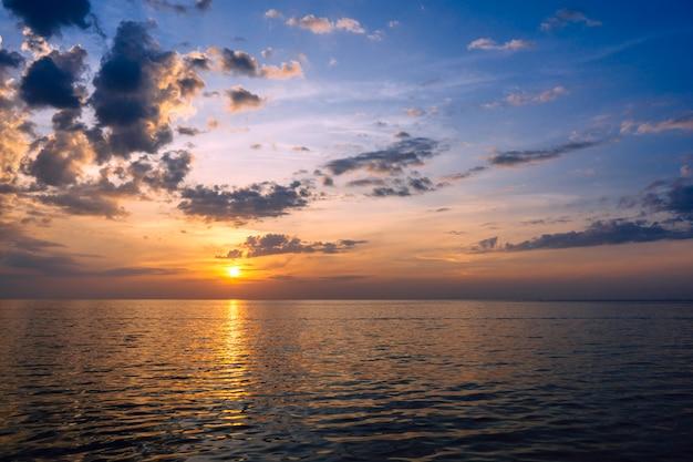 Geweldige zomer zonsondergang uitzicht op het strand. mooi laaiend zonsonderganglandschap bij de zwarte zee en de oranje hemel erboven met ontzagwekkende zon gouden bezinning op kalme golven als achtergrond.