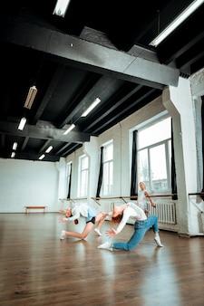 Gewelfd op de vloer. professionele balletleraar gekleed in een spijkerbroek en haar doet boog