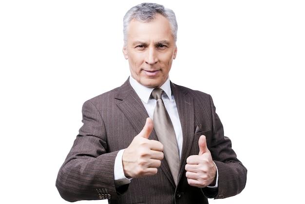 Gewend aan succes. zelfverzekerde volwassen man in formalwear die zijn duimen opsteekt en glimlacht terwijl hij tegen een witte achtergrond staat