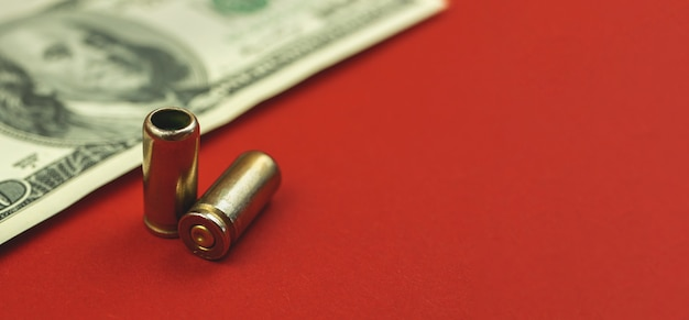 Geweren en geld, kogel en dollar op rode achtergrond, crimineel en illegaal concept, kopieer ruimtefoto