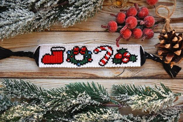Geweven vriendschapsarmband met patroon kerstbes lolly krans en santas laars